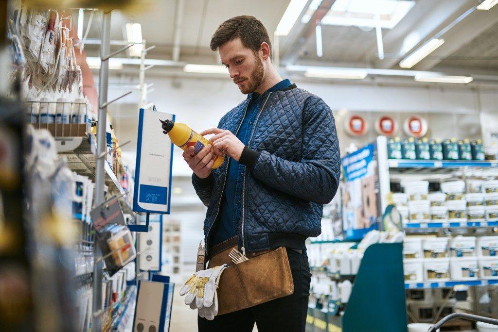 man checking mustard product label