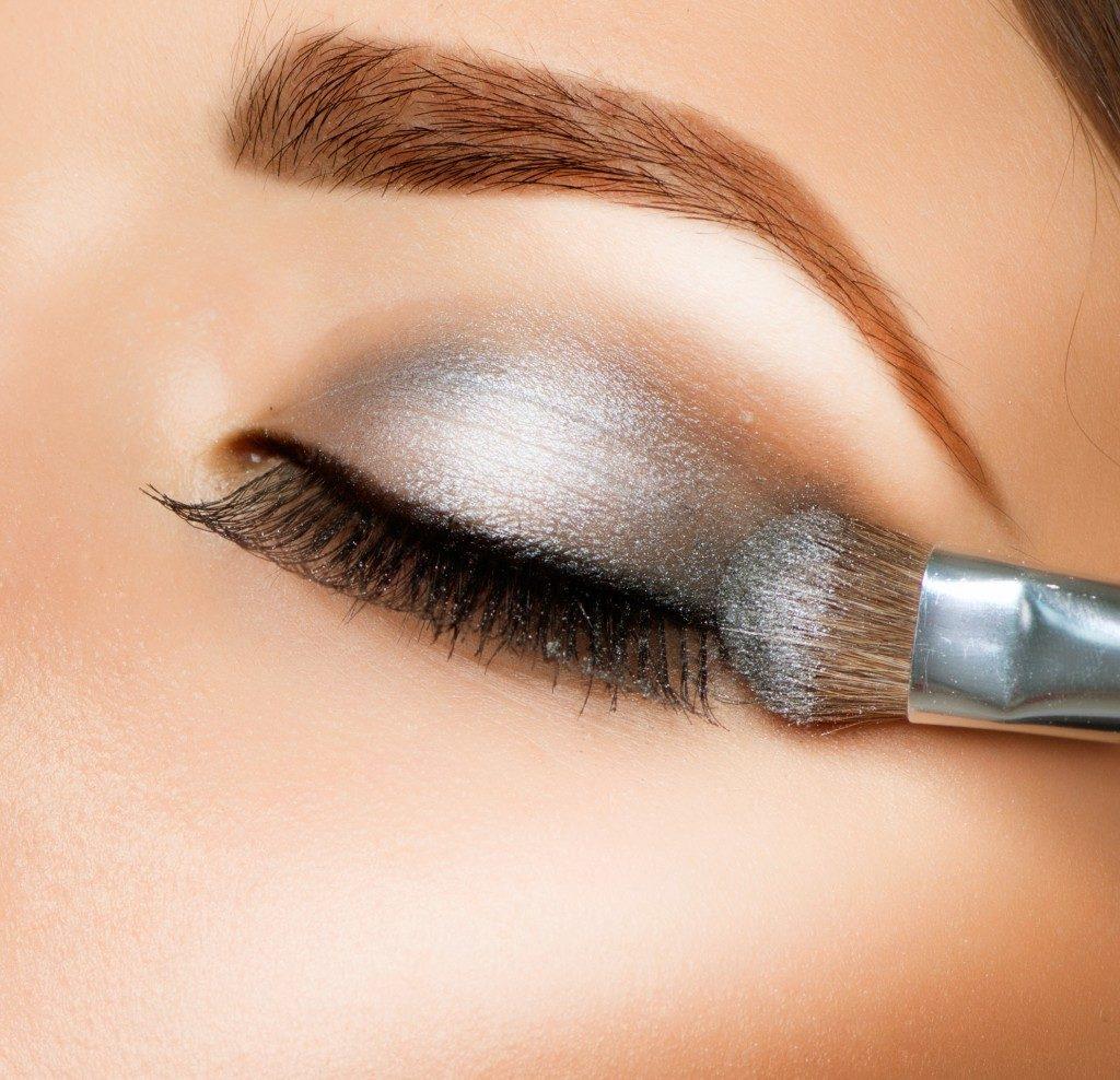woman applying gray eyeshadow